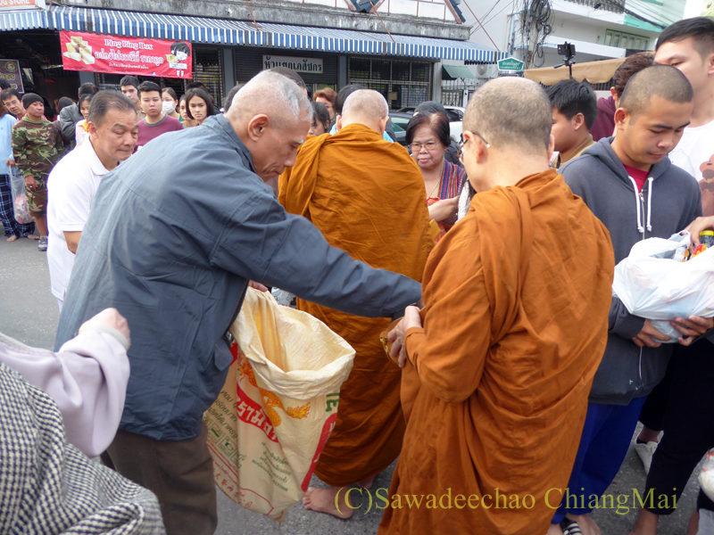 チェンマイ元旦朝の特別托鉢でお供え物を移し替える寺男