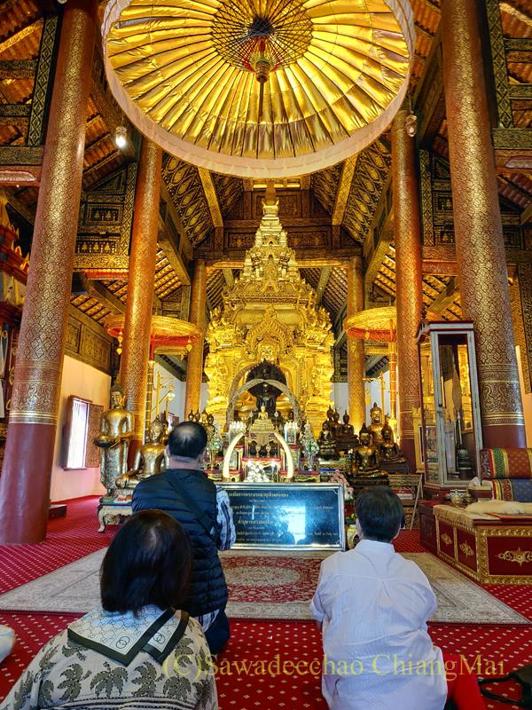 チェンマイ郊外にある寺院ワットプラタートシーチョムトーンに祈りをささげる人々