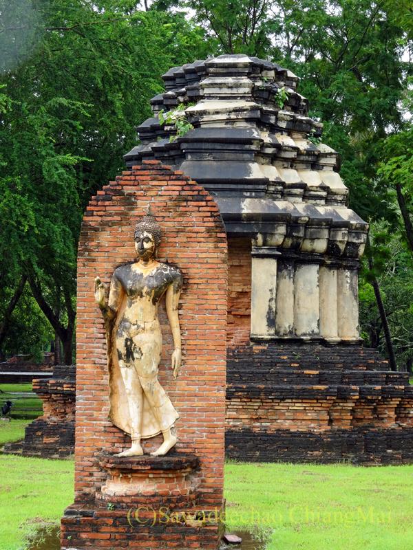 タイのスコータイ遺跡のワットトラパンングンの遊行仏像と仏塔