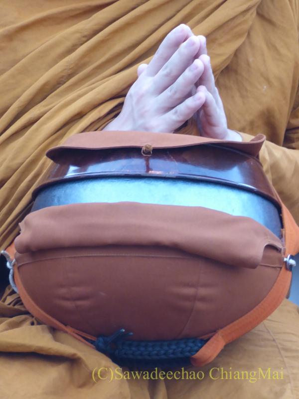 チェンマイの元旦の特別タムブンで読経する僧侶の鉢と手