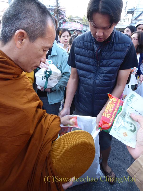 チェンマイの元旦の特別タムブンで鉢からあふれそうなお布施を頭陀袋に移す