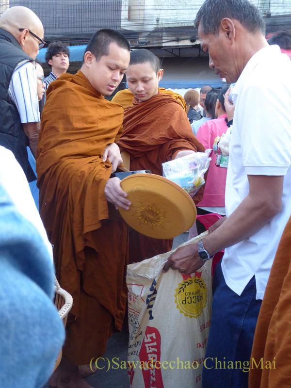 チェンマイの元旦の特別タムブンで鉢からあふれたお布施を頭陀袋に入れる僧侶