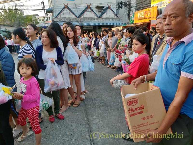 チェンマイの元旦の特別タムブンで托鉢布施するために並んだ人々
