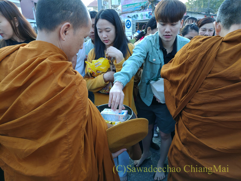 チェンマイの元旦の特別タムブンで鉢にお布施を受ける僧侶たち
