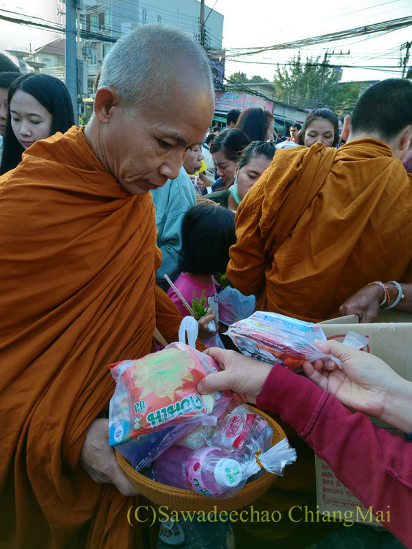 チェンマイの元旦の特別タムブンで鉢にお布施を受ける僧侶