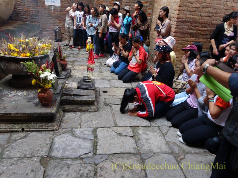 タイのスコータイ遺跡のワットシーチュムのアチャナ仏に祈りをささげる人々