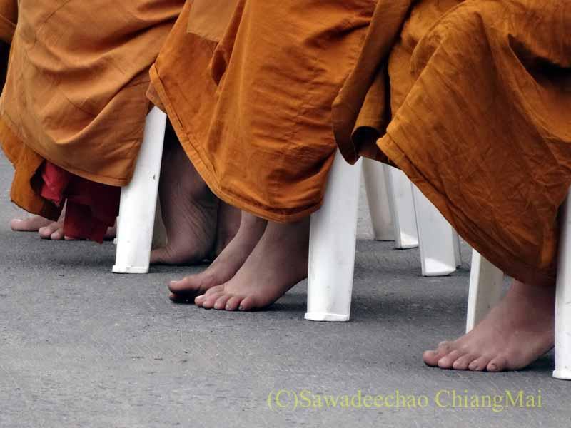 チェンマイの元旦の特別タムブンで読経するする僧侶の足
