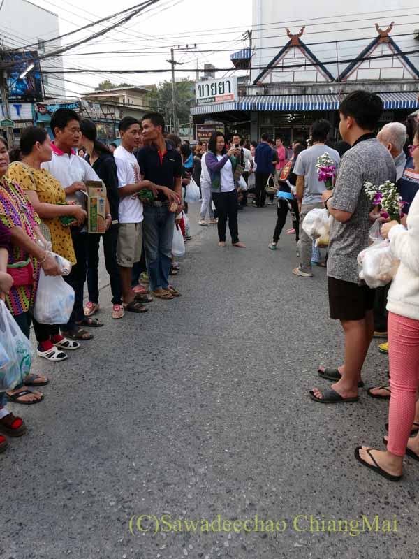 チェンマイの元旦の特別タムブンで僧侶に供養するために列を作る人々