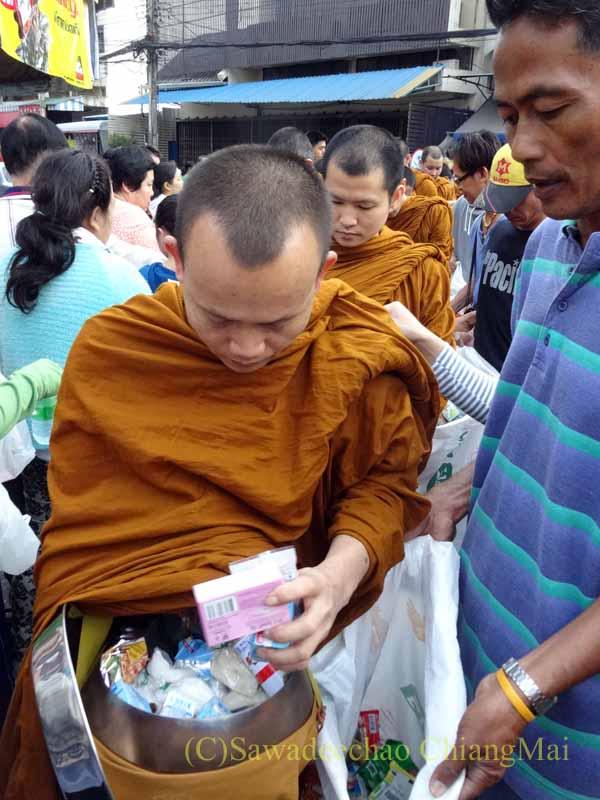 チェンマイの元旦の特別タムブンで供養物をずだ袋に入れる僧侶