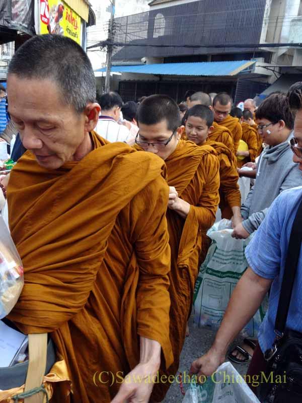 チェンマイの元旦の特別タムブンで托鉢をする僧侶の列