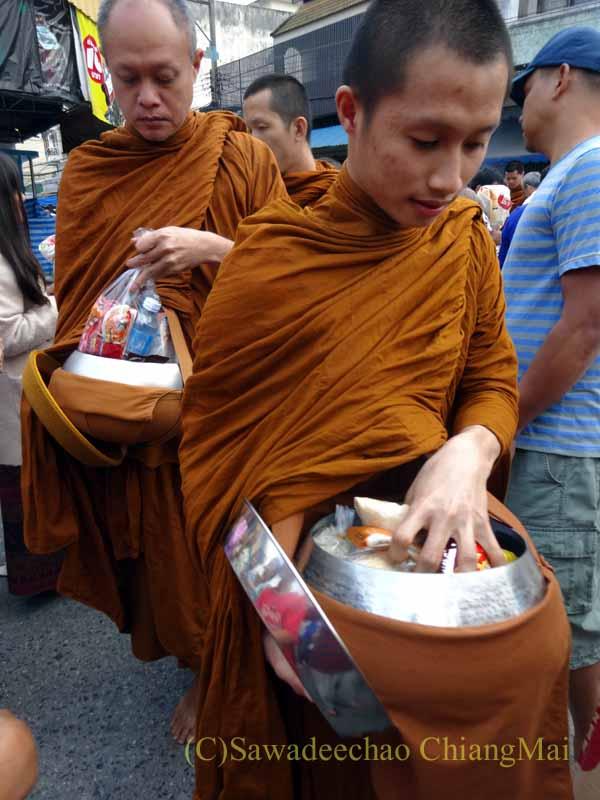チェンマイの元旦の特別タムブンで鉢を持って供養物を受け取る僧侶
