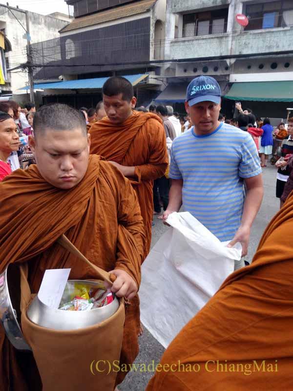 チェンマイの元旦の特別タムブンで供養物を入れるずだ袋を持つ寺男