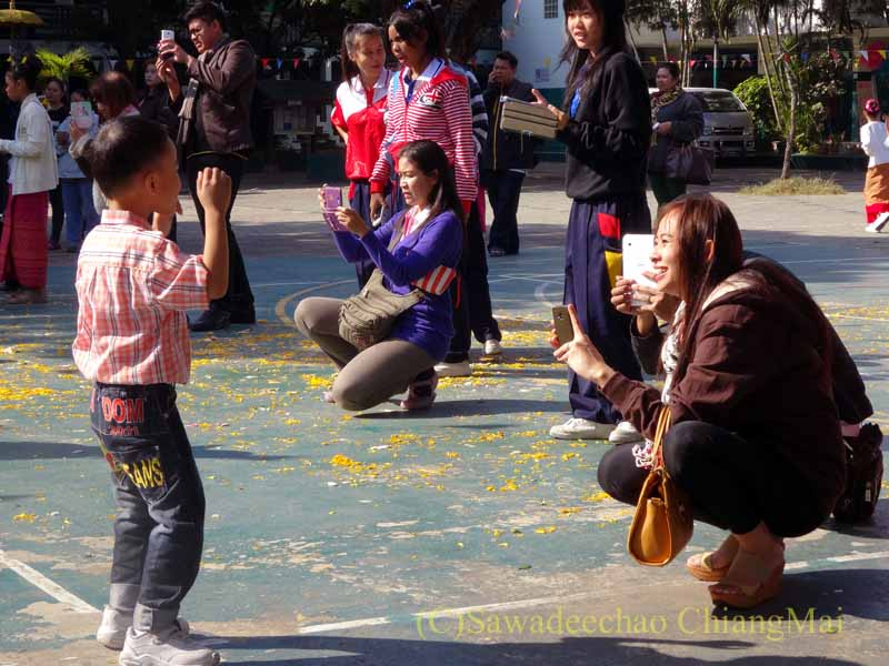 チェンマイ市内の学校で行われた学芸会でダンスをする子供を撮影する親