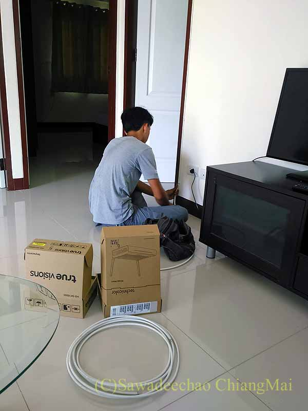 CATVのセットトップボックスとwifiルーターを設置するTRUEの作業員