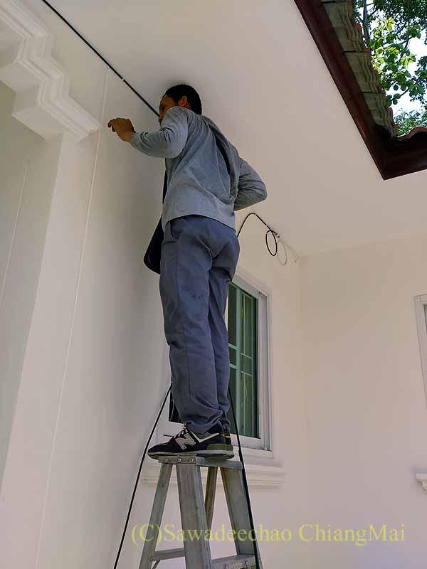 チェンマイの自宅の壁にネットのケーブルを敷設するTRUEの作業員