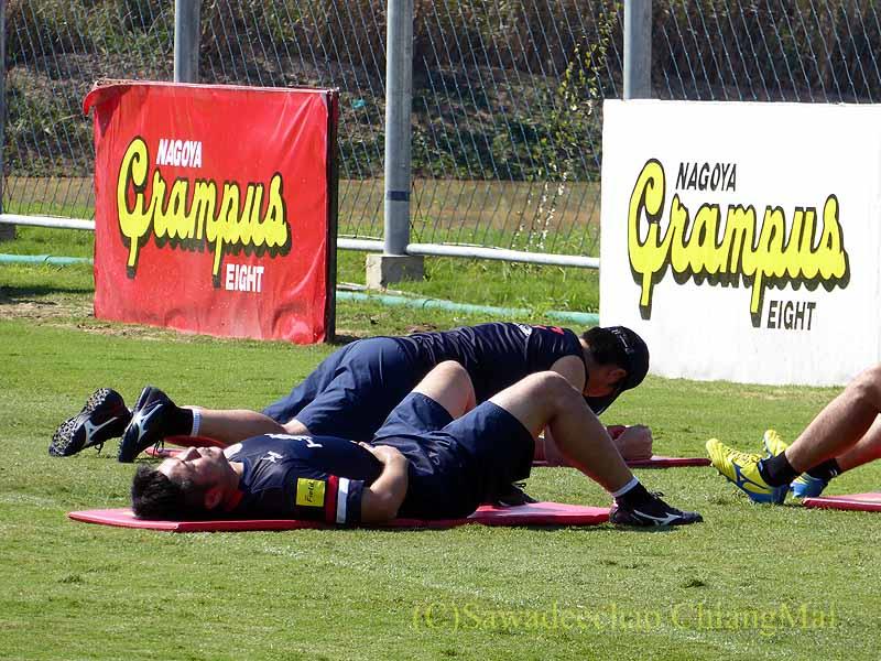 チェンマイでのサッカーJ2名古屋グランパスのキャンプでストレッチをする選手