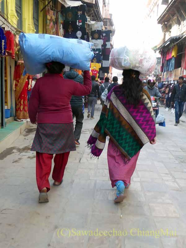 ネパールのカトマンズ旧市街で荷物を頭に乗せて運ぶ女性