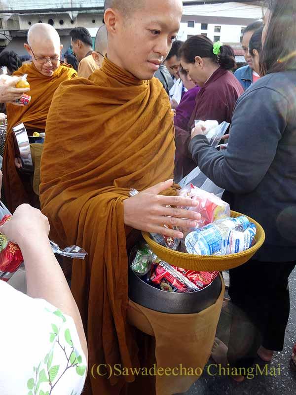 チェンマイ市内の元旦特別タムブン(徳積行)にやって来た僧侶の鉢の供養物
