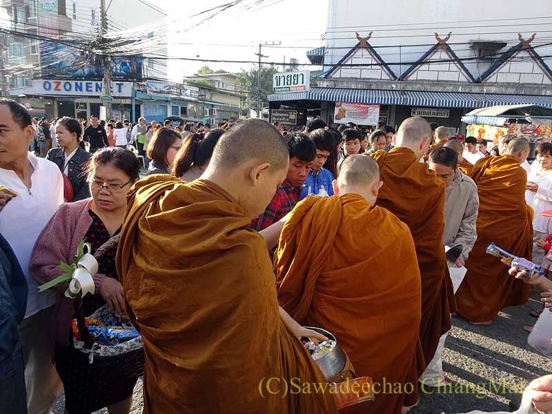 チェンマイ市内の元旦特別タムブン(徳積行)でに托鉢を受ける僧侶たちと人々