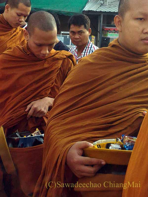 チェンマイ市内の元旦特別タムブン(徳積行)でに托鉢を受ける僧侶の列