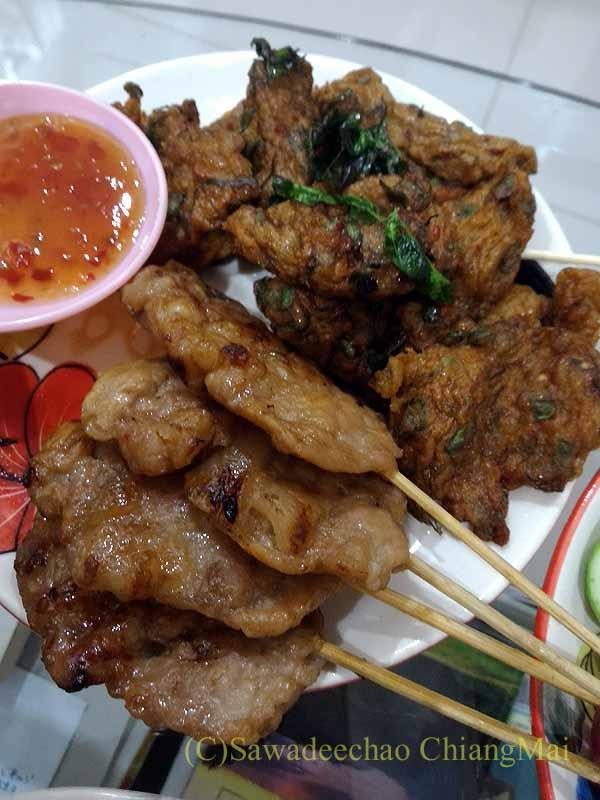 チェンマイ郊外で開催れる定期市で購入した豚串焼きとタイ風さつま揚げ