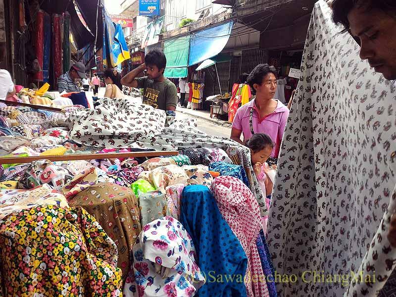 チェンマイのワローロット市場の布地屋で量り売りの布を買う