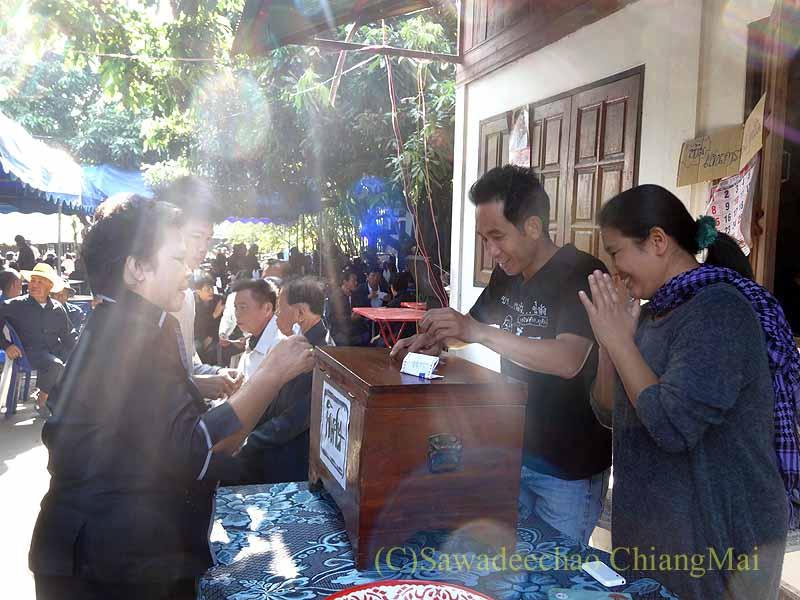 チェンマイ郊外の田舎の村での葬儀の香典渡し