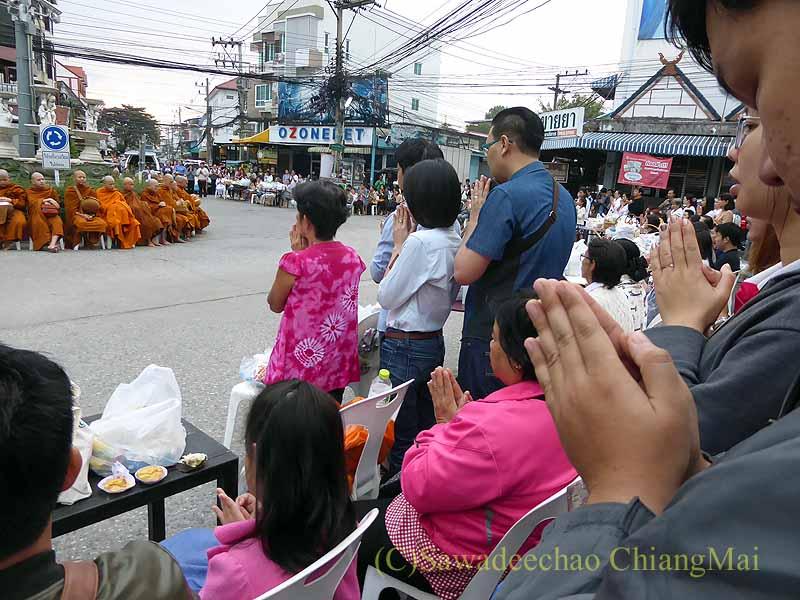 チェンマイ市内の元旦特別タムブン(徳積行)の読経に合わせ祈る人々