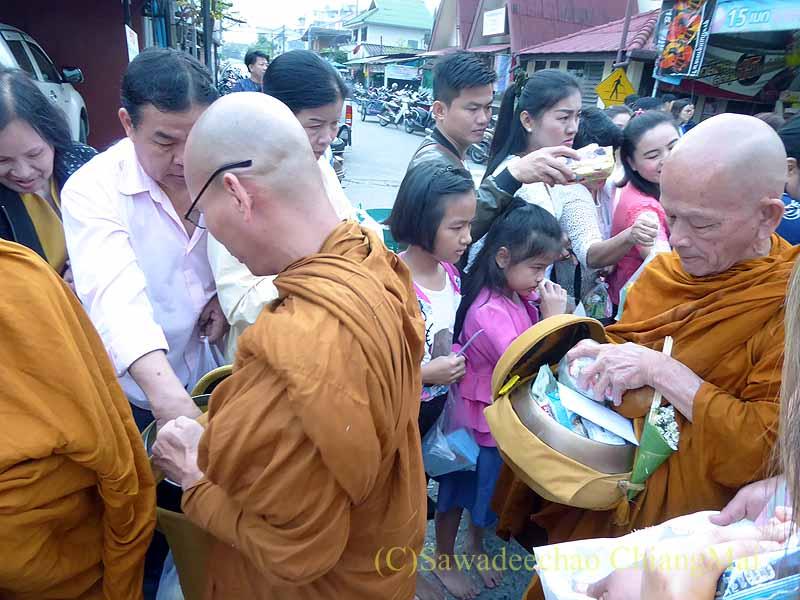 チェンマイ市内の元旦特別タムブンで供物を受け取る僧侶