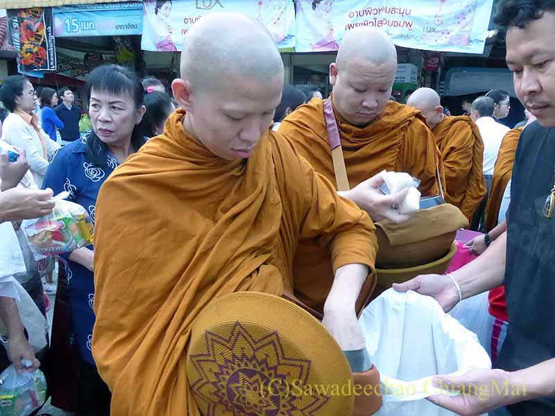 チェンマイ市内の元旦特別タムブンで鉢に供物を入れる人
