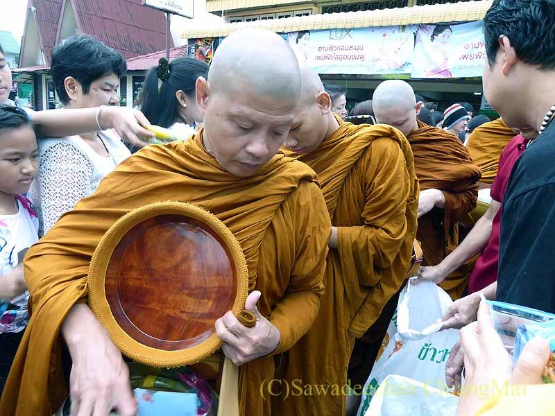 チェンマイ市内の元旦特別タムブンで鉢を持って歩く僧侶