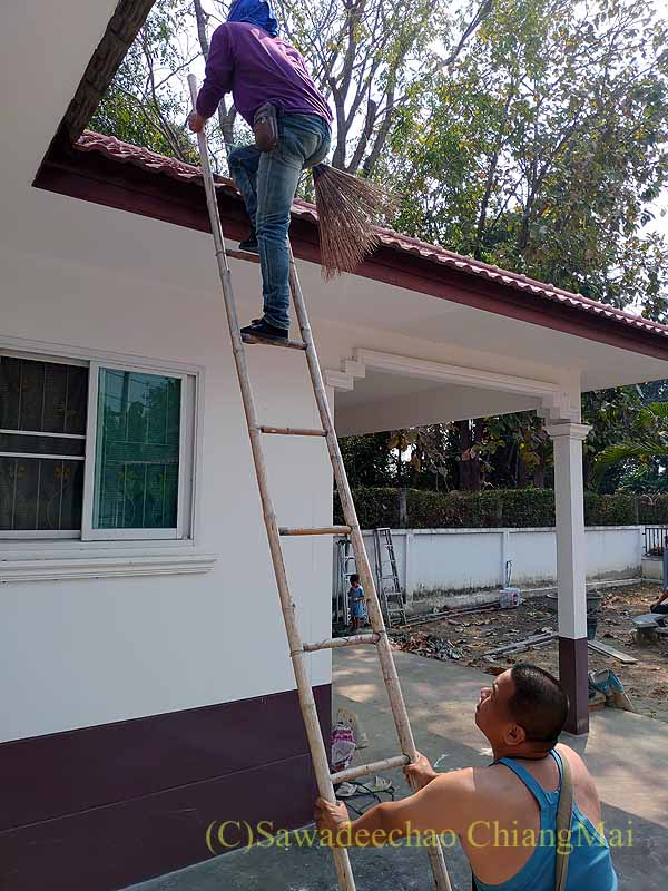チェンマイの自宅の修繕工事で屋根に登る職人
