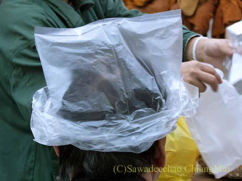 チェンマイの特別タムブンで頭にビニール袋をかぶる人