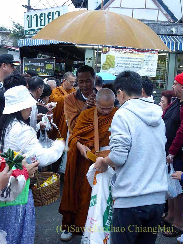 チェンマイの特別タムブンで人々の間を通る僧侶