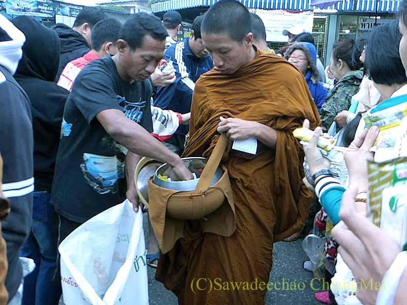 チェンマイの特別タムブンで僧侶の鉢から供え物を出す寺男