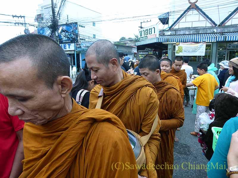 チェンマイの特別タムブンで人々から供え物を受け取る僧侶