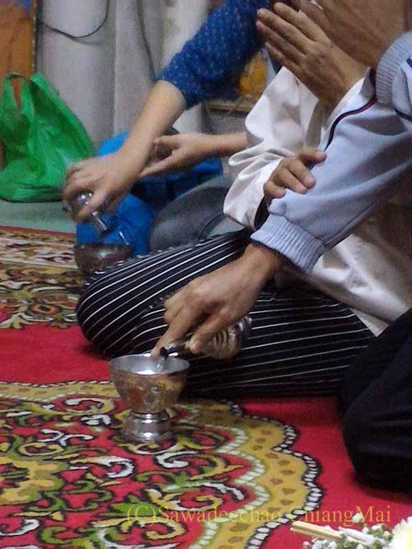 チェンマイの寺院での厄祓いの儀式での聖水こぼし
